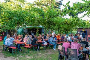 Viele Gäste sitzen auf Bierbänken vor der Bühne im Vogelpark